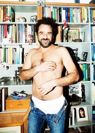 Hassan Preisler står i bar overkrop og opknappede bukser foran sin bogreol og griner