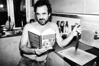 Hassan Preisler står i sit køkken med en bog af Carl-Mar Møller og en køkkenkniv