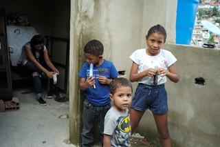 Drei Kinder – zwei Jungs, ein Mädchen – im Grundschul- und Kindergartenalter stehen vor einer nackten Betonwand
