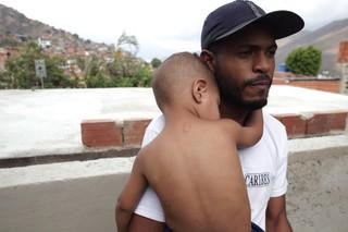 Armando hält seinen Sohn im Arm