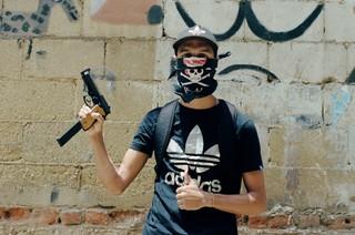 Ein Mann mit Basecap, T-Shirt und einem Tuch vor dem Gesicht hält eine Pistole hoch und reckt den Daumen der anderen Hand