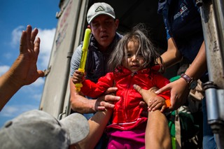 To move migrants our of Mexico City an on to their next destination, state workers helped migrants get rides in the back of cargo trucks. (State of Mexico, Mexico)