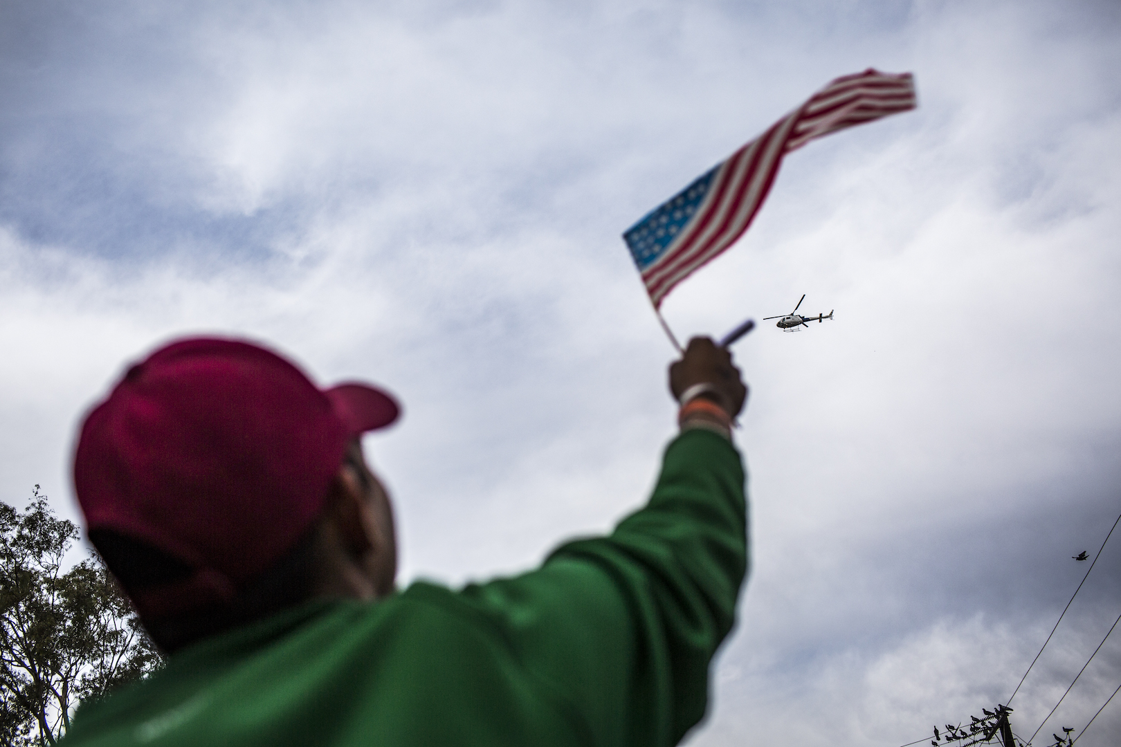 A migrant waves an American flag to a helicopter flying above the migrant shelter just along the U.S.-Mexico border in Tijuana, Mexico. (Jika Gonzales/VICENews).