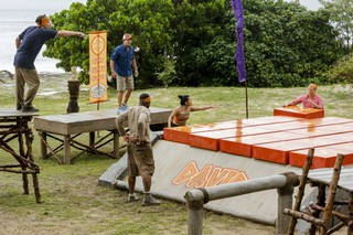 Survivor contestant Christian directs teammates to complete a puzzle.
