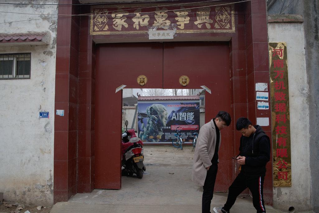 右边的周俊凯和他的堂兄陈锐站在他们办公室的门外。