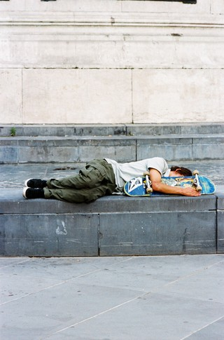 A skateboarder fast asleep with his board.