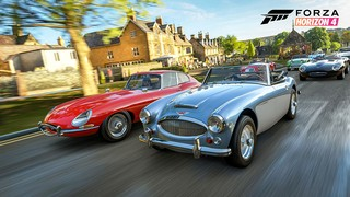 Old British sports cars go racing through a village