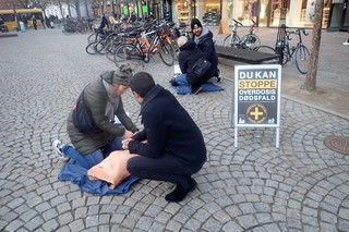 Tina Leth Hansen og en frivillig ung mand viser sidder bøjet over en dukke, som de udøver førstejælp på