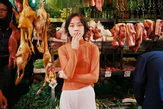 luo yang photographs a woman smoking in a market
