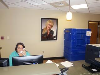 Žena u bolničkoj uniformi se javlja na telefon ispred portreta Doli Parton