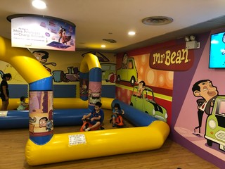 Children drive karts around an inflatable track with Mr. Bean cartoons on the wall