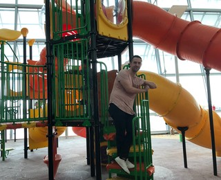 a man stands on a playground jungle gym that is inside an airport
