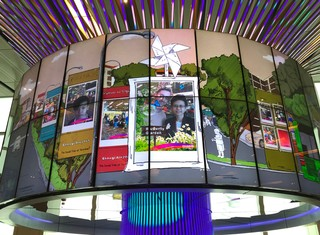 An lcd screen displays photo booth pictures of travelers