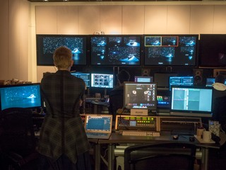 Rehearsal image, Producer Lisa Niedermeyer stands with her back to us and facing a dozen monitors in the video control room of EMPAC rehearsing the livestream of DESCENT. Five different cameras show the opening image of Andromeda among the stars from different points of view. The angle framed is red is the one streaming, and angle framed is yellow is cued up to go next.