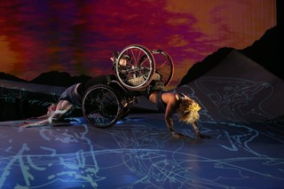 Alice Sheppard and Laurel Lawson partner, with their wheelchairs joined, at the base of the ramp in a performance of DESCENT.