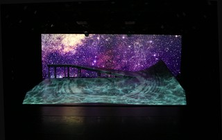 The ramp, spanning 24 by 15 feet across the stage, with the righthand peak reaching six feet. Throughout DESCENT it is illuminated with art, landscapes and stars projected by Michael Maag.