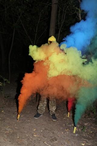 mężczyzna stojący w kolorowym dymie