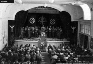 1547028699706-koncert-SS-orkestra-na-nepoznatoj-lokaciji-u-okolini-Beograda-moguce-u-Pancevu-sala-je-ukrasena-runama-pseudomitskim-motivima-izmisljenim-za-lazni-istorijski-imidz-SS-formacija