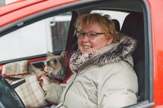 Eine Frau in ihrem Auto bietet sich als Mitfahrgelegenheit an