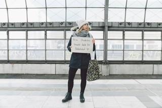 Unsere Autorin hält auf dem Bahnsteig ihr Schild hoch