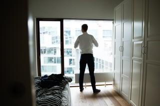 Rasmus Brygger står foran sit vindue og tager skjorte på
