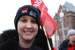 Kaitlyn Teller, a support staff worker at UOIT, waves a banner during the protest against tuition cuts and ancillary fee changes on Jan. 19 at Queen's Park. Photo: Emma Sandri