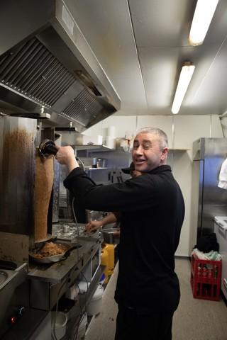 Baki er i gang med at skære kød til shawarma på Ørestad Kebab