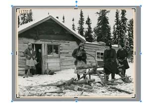 Screenshot Fotobearbeitung. 1945, Kanada: Frauen sägen vor einer Hütte Brennholz