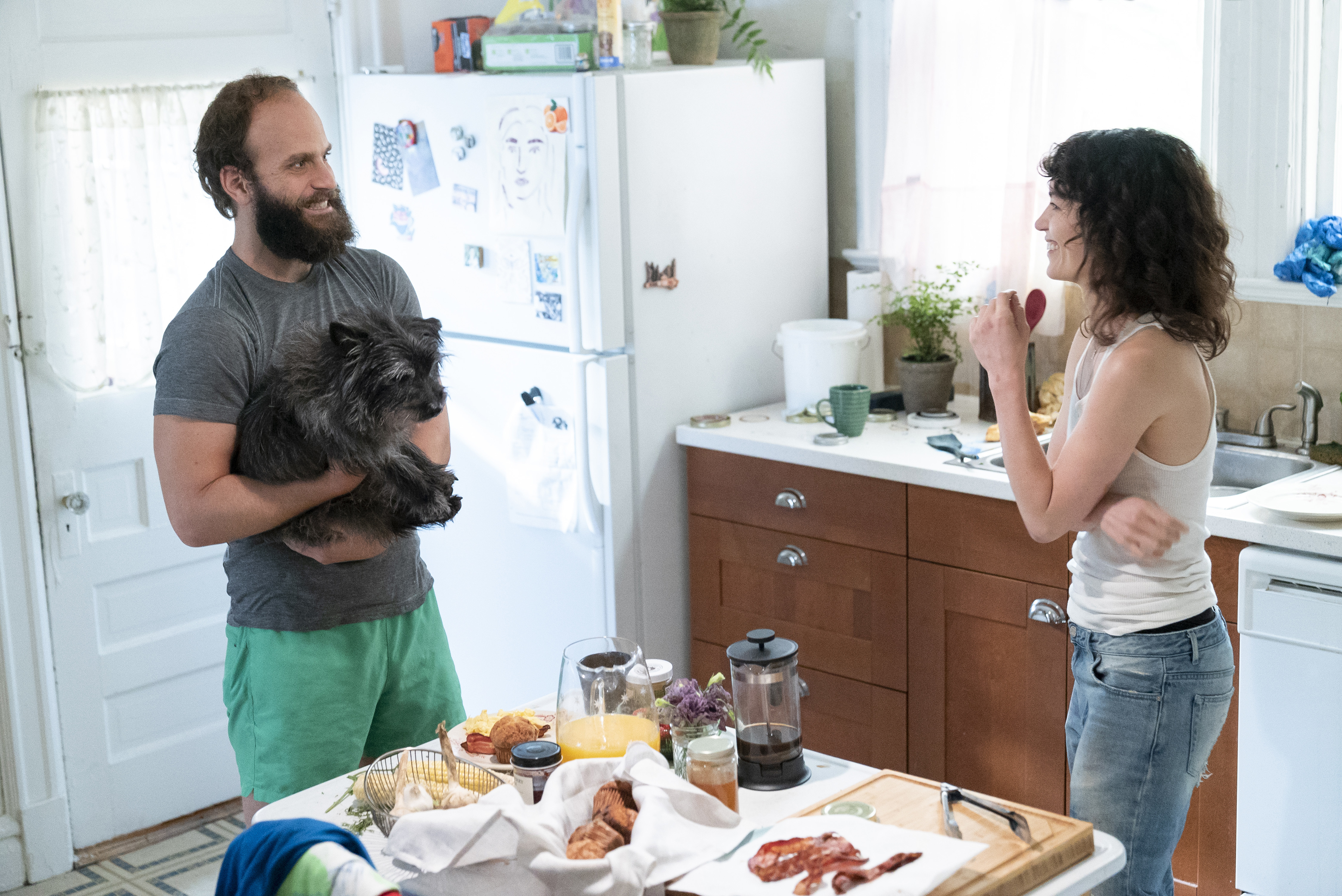 The Guy (Ben Sinclair) holds a dog in the kitchen while talking to Lee (Britt Lower) in season three of HBO's 'High Maintenance.'