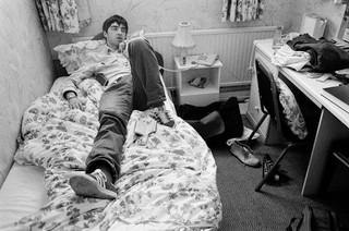 Oasis's Noel Gallagher in bed and on the phone.