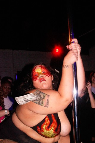 A stripper in a msk, clinging on to a pole