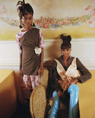 Eniola (left) wears dress by SNOW XUE GAO, earrings by DANNIJO; Tami (right) wears top, jacket, and trousers by MAISON MARGIELA, earrings by AREA.