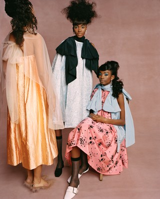 From left: Lineisy wears veil, dress, and shoes by SIMONE ROCHA; Tami wears dress, stockings, and shoes by ERDEM,earrings byFALLON;Imari wears dress, stocking, and shoes by ERDEM, earrings by FALLON