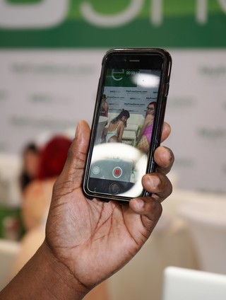 A man's hand holding a cell phone as he takes a photo of two women twerking