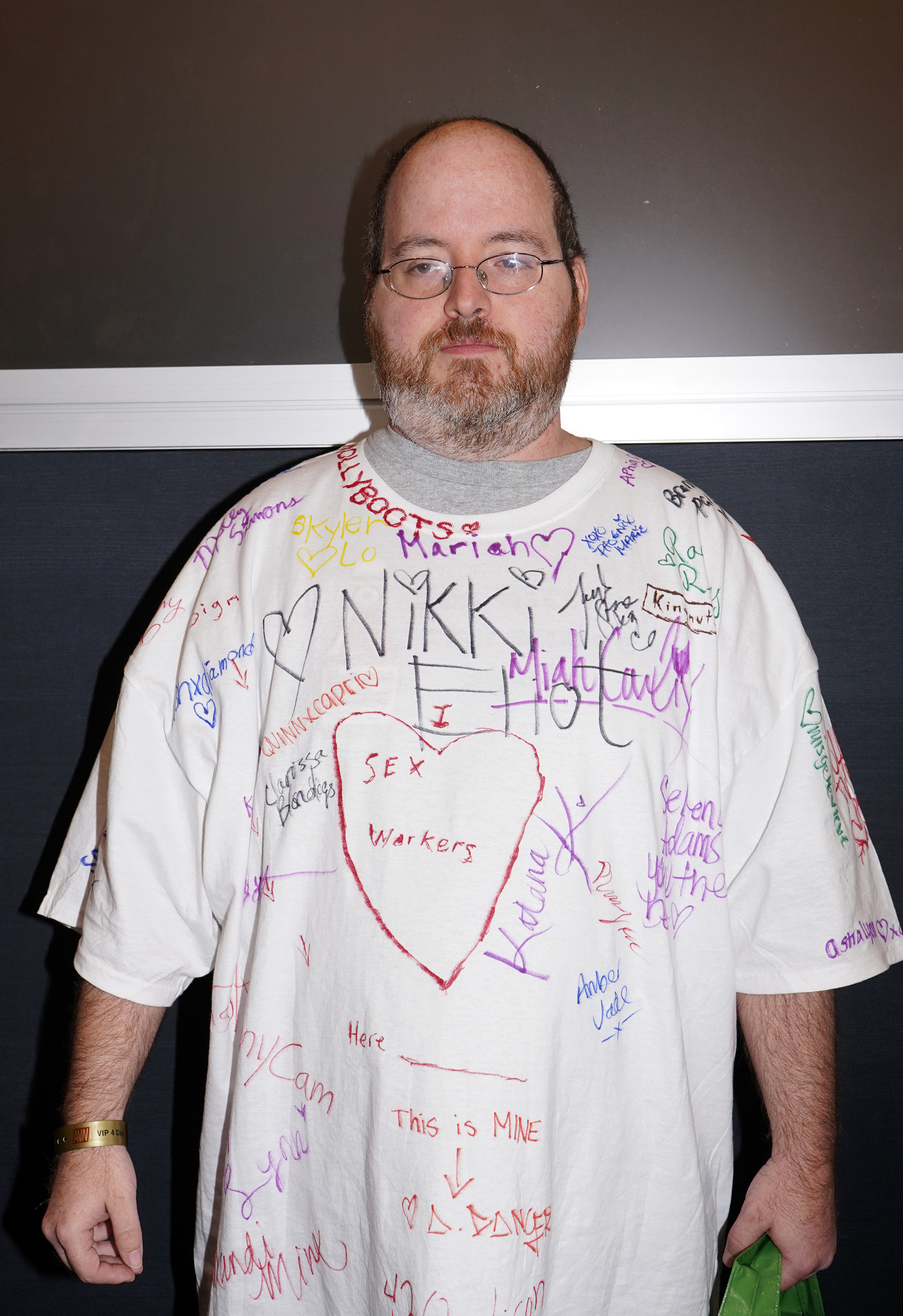 A man wearing a T shirt covered in the signatures of porn actors and cam models
