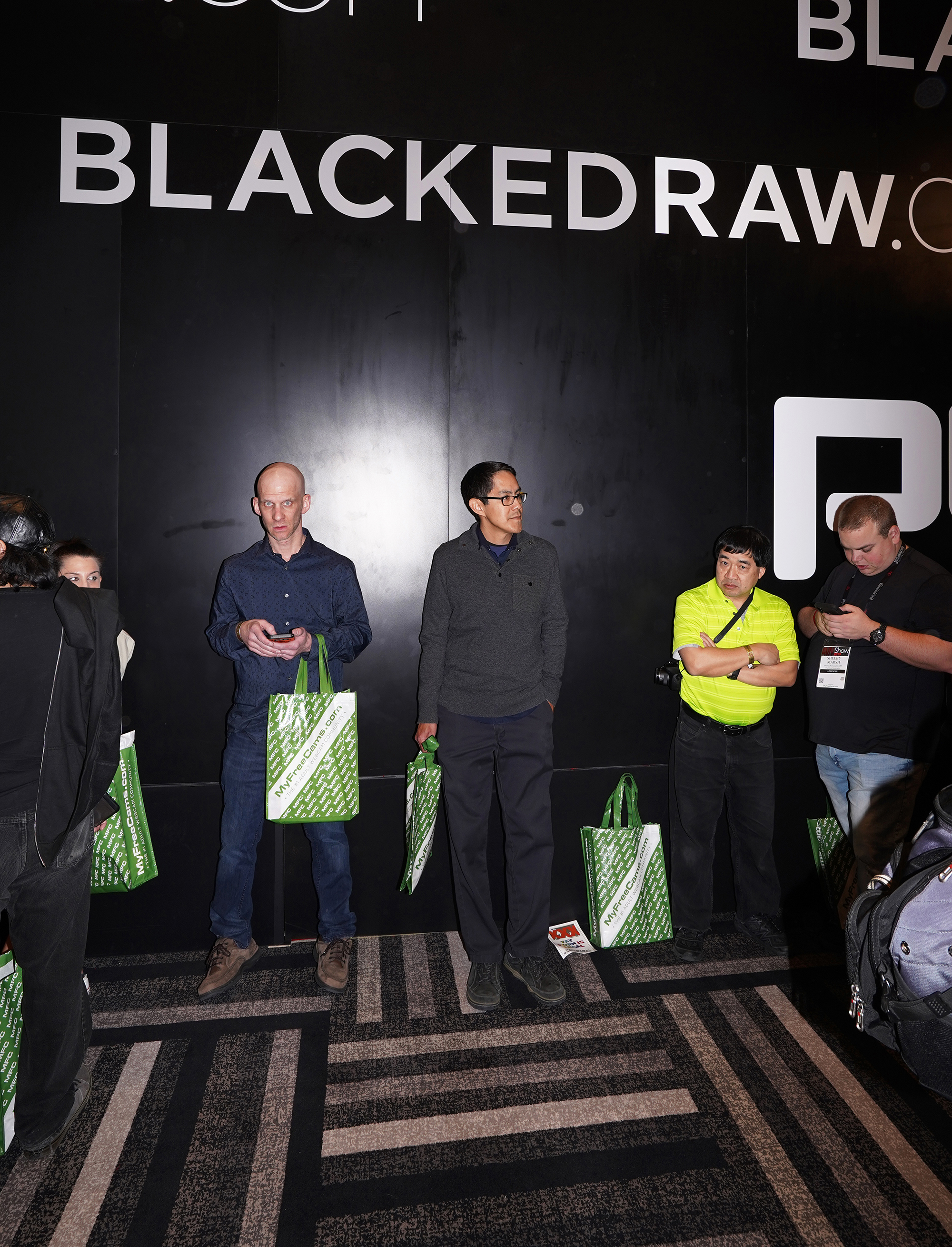 A group of porn fans lining up under an advertisement for BlackedRaw