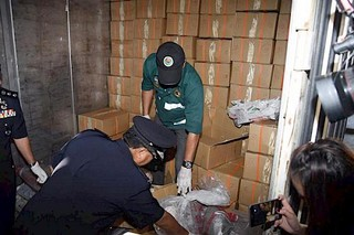 Customs officers inside one of the containers which included 1,800 boxes full of frozen pangolins.