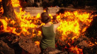 A Far Cry: New Dawn character composes an image before a burning field, arms and fingers outstretched to mimic the frame of a camera.