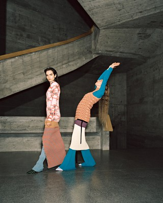 Lily (left) wears top and skirt by PACO RABANNE, pants and underpinning by ACNE STUDIOS, earrings by CULT GAIA; Martje (right) wears vest and skirt by JIL SANDER, shirt and trousers by ELLERY, earrings by CULT GAIA, all shoes by AMY CROOKES.