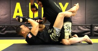 Two MMA fighters grappling on the mat