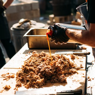 barbecue sauce being poured onto chopped meat at hot luck festival