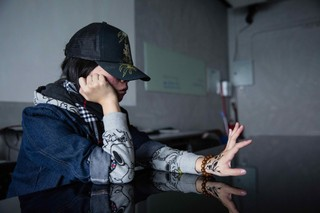 Tung, a recovering hikikomori, stares at a drawing of a fish on her hand.