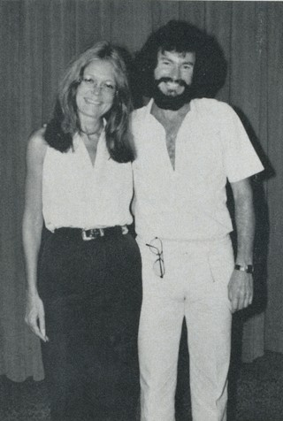 Gloria Steinem standing and smiling next to Warren Farrell