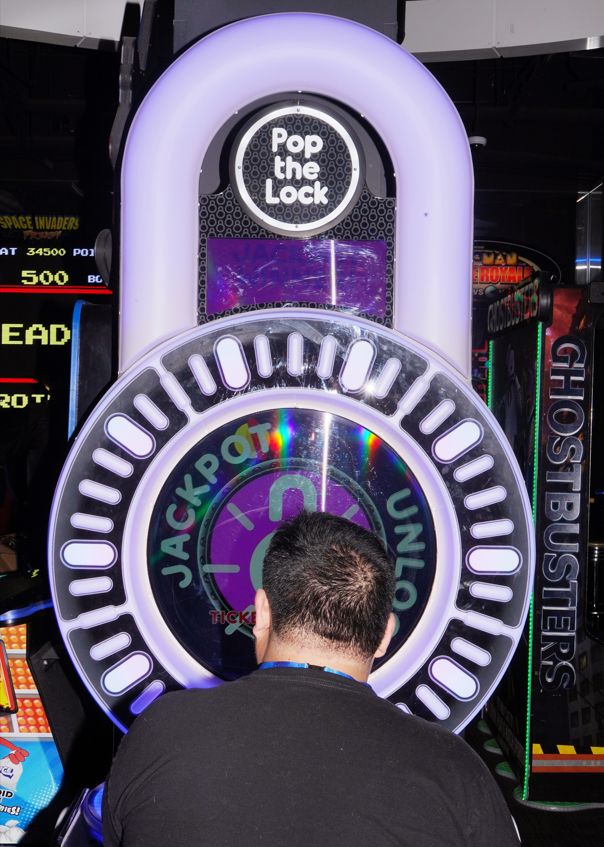 The back of a man's head as he plays an arcade game called 'Pop the Lock'