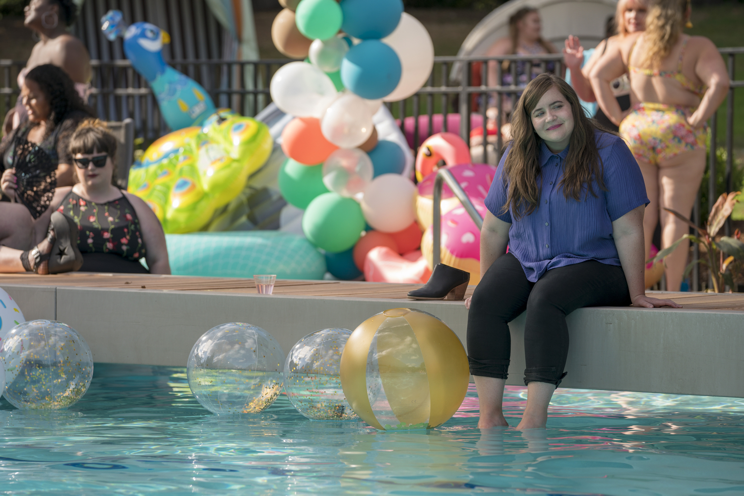 Aidy Bryant with her legs in the pool
