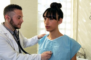 A transgender woman in a hospital gown being treated by a doctor, a transgender man.