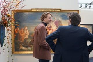 man staat samen met andere man voor schilderij