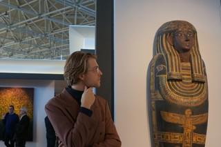 man naast een farao beeld