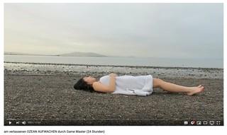 Screenshot von YouTube. Thi Lan liegt auf dem Rücken auf einem Kiesstrand. Über ihr ein Handtuch. Im Hintergrund: Meer und eine Insel