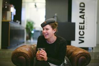 Vrouw met baret met glas lacht terwijl ze op stoel zit